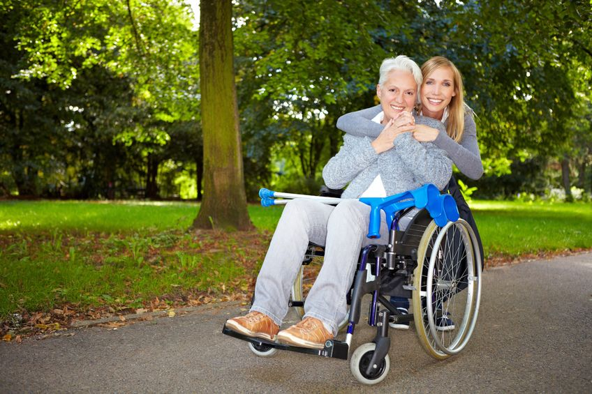 8287050 - granddaughter embracing her grandmother in wheelchair outdoors